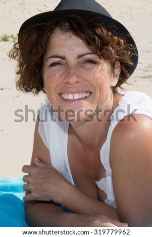 Woman, 40, brunette with hat and freckles at the beach on holidays - stock photo