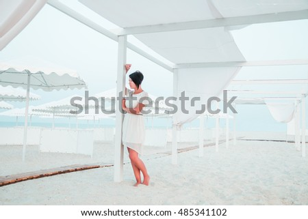 Woman, brunette with short hair in white dress on the beach of ocean, sea near sun shade, tent. Vacation.