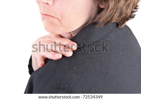 Woman brushing dandruff off of her shoulder - stock photo