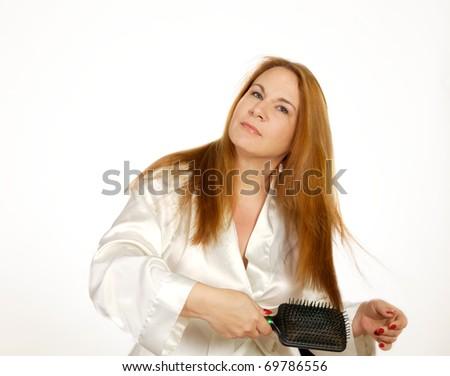 Woman brushing hair while wearing robe.  Shot in studio on white background - stock photo
