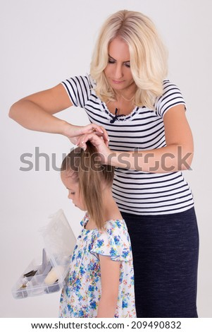 woman brushing her daughter hair over white background