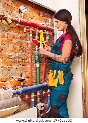 Woman  builder fixing heating system with special tool. - stock photo