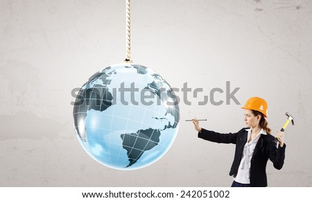 Woman builder hitting nail with hammer in digital globe - stock photo