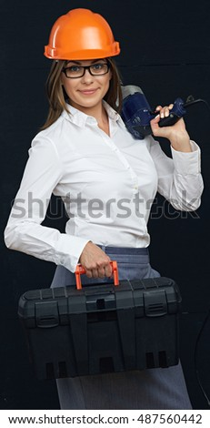 Woman builder with box tools holding drill on shoulder. Black background.