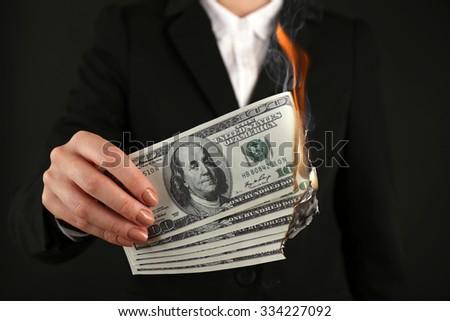 Woman burning  dollars closeup - stock photo
