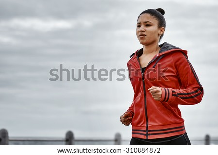 Woman busy jogging along the ocean side in the morning to keep active and always keep moving forward - stock photo
