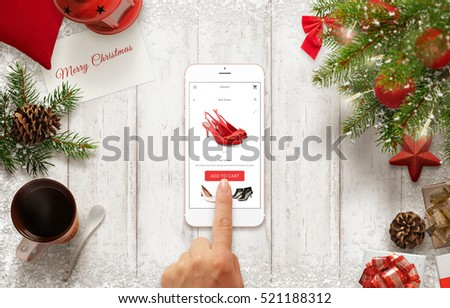 Woman buy shoes online with mobile phone during Christmas time. Table with Christmas decorations. Christmas tree and gifts beside.