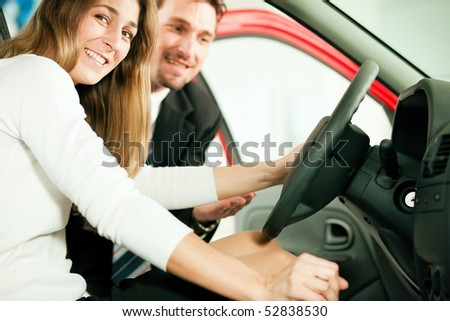 Woman buying a car in dealership sitting in her new auto, the salesman talking to her in the background - stock photo