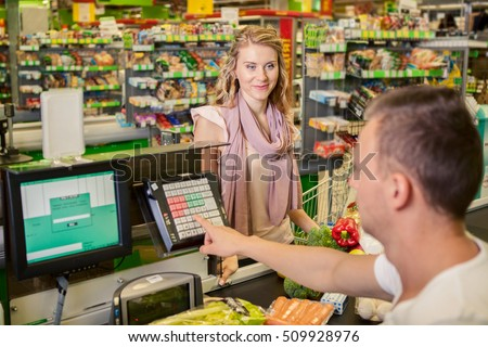 Woman buying food at supermarket and making check out with cashdesk worker in store