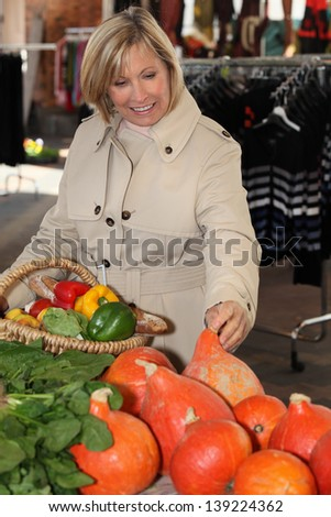 Woman buying fruit at the market - stock photo