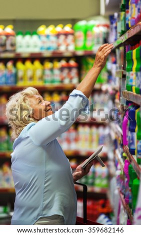 Woman buying household detergents in the shop - stock photo