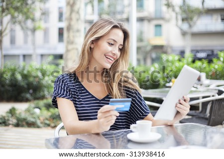 Woman buying online with a tablet and a credit card in a terrace bar - stock photo