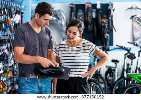 Woman buying parts in bike shop - stock photo