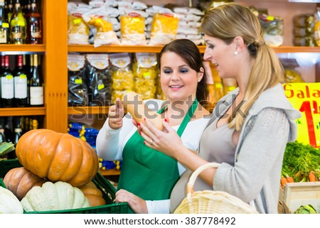 Woman buying pumpkin and vegetables in delicatessen - stock photo