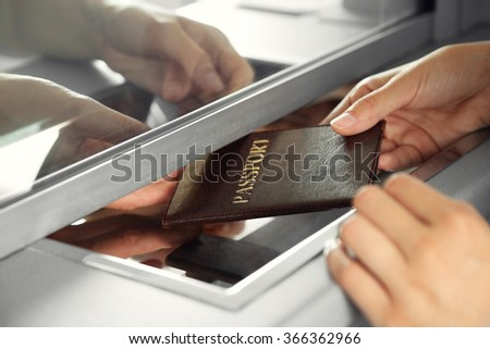 Woman buying tickets with passport at box office - stock photo