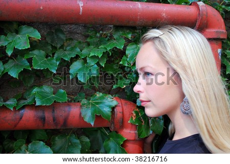 Woman by pipes and a vine covered wall - stock photo