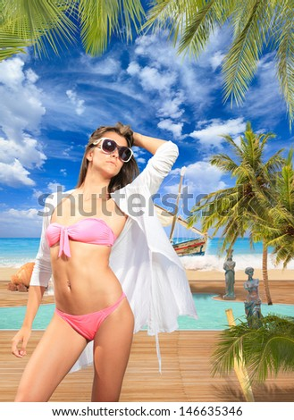 Woman by the swimming pool at luxury tropical resort - stock photo