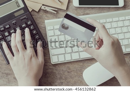 woman calculate how much cost or spending have with credit cards. Low light, selective focus on hand, can be used for e-commerce, business, technology and internet concept, Vintage tone filter - stock photo