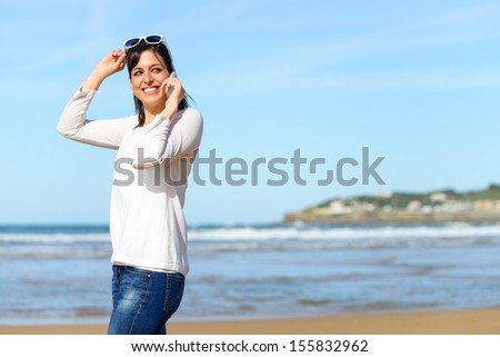 Woman calling by cell phone and walking on beach. Brunette woman on travel vacation mobile conversation smiling. - stock photo