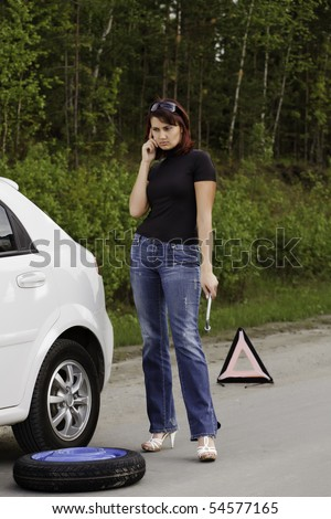 Woman calling to a service standing by a white car.