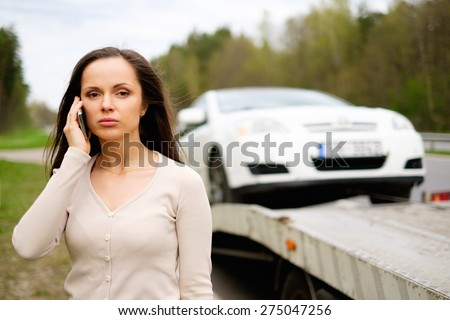 Woman calling while tow truck picking up her car - stock photo