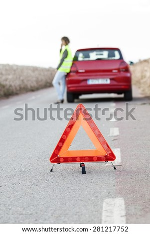 Woman calls to a service standing by a red car. Focus is on the red triangle sign. Evening light. - stock photo