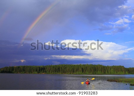 Woman canoeing in a beautiful lake with rainbow in the sky - stock photo
