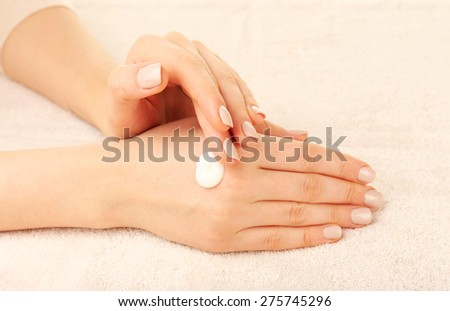 Woman caring hands with cream on fabric background - stock photo