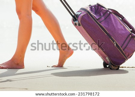 Woman carries your luggage at sandy beach, Bali, Indonesia - stock photo