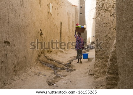 Woman carrying basket on head in narrow street - stock photo