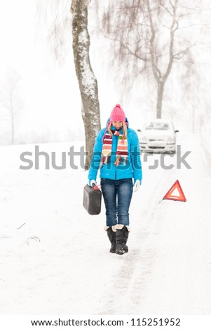 Woman carrying gas can snow car trouble winter breakdown walking - stock photo
