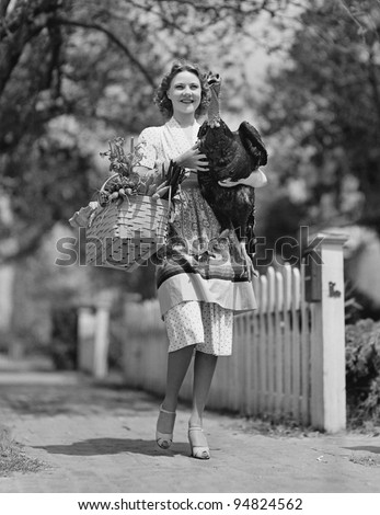 Woman carrying live turkey and grocery basket - stock photo