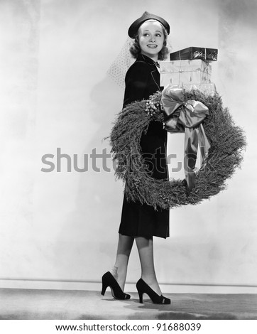 Woman carrying packages and Christmas wreath - stock photo
