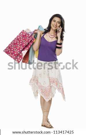 Woman carrying shopping bags and talking on mobile phone