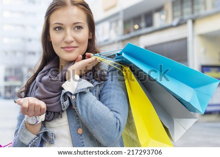 Woman carrying shopping bags while looking away - stock photo