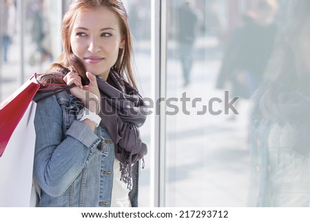 Woman carrying shopping bags while standing by store - stock photo