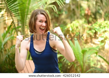 Woman celebrating reaching her goal with a big smile - stock photo
