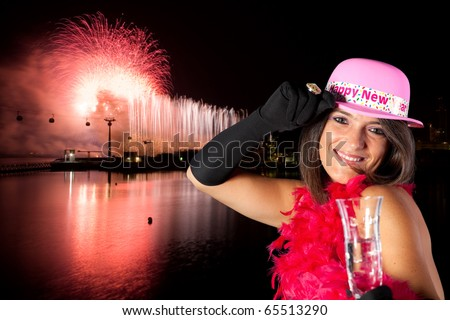 woman celebrating the new year eve with firework as background - stock photo