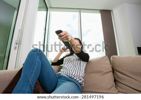 Woman changing channels while watching TV on sofa at home - stock photo