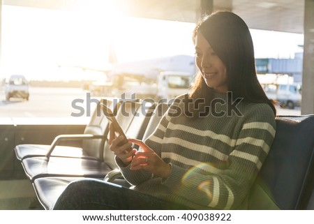 Woman chat on cellphone at airport - stock photo