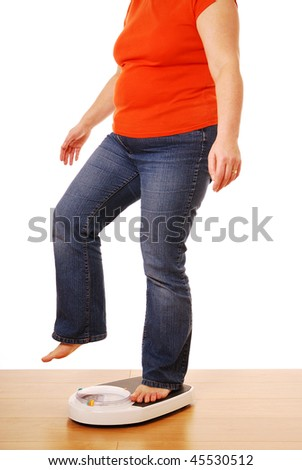 Woman cheating on weighing scales - stock photo