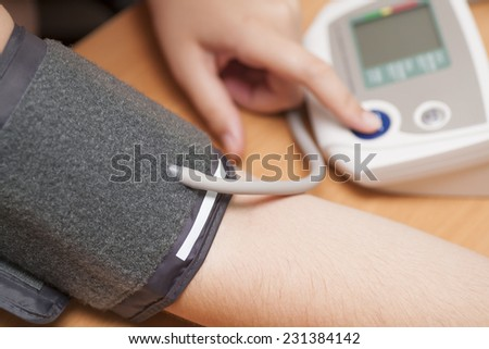 Woman checking blood pressure and heart rate with a digital blood pressure monitor. - stock photo