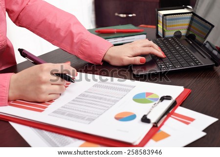 woman checking budget or payroll with laptop - stock photo
