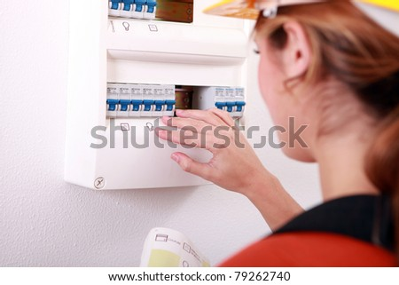 Woman checking electric meter - stock photo
