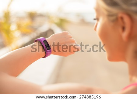 Woman checking fitness and health tracking wearable device - stock photo