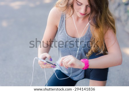 Woman checking her fitness smart watch device - stock photo