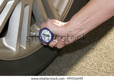 Woman checking her tire pressure to help increase her gas mileage - stock photo