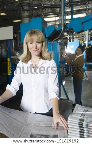 Woman checking newspaper with colleague in the background in factory - stock photo