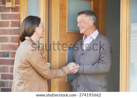 Woman Checking On Elderly Male Neighbor - stock photo