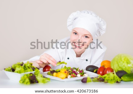 Woman chef dressed in white cook uniform decorating vegan dish with green salad